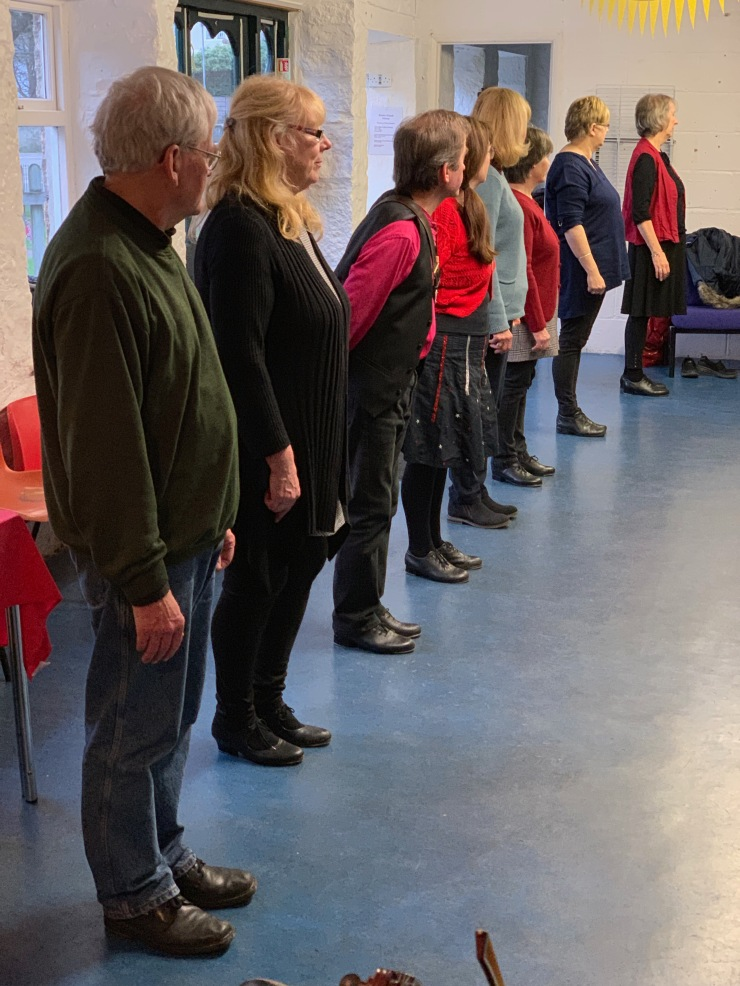 Photograph showing a line of beginners with Tros an Treys dancers at Penlee Coach House.